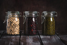 Red, Green And White Beans In Jars On A Dark Wooden Rustic Table. Vegan And Vegetarian Food.