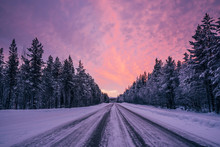 Remote Winter Road Through Snow Covered Forest Trees Against Dramatic Purple Pink Sky, Lapland, Finland
