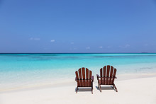 Two Adirondack Chairs On Sunny, Tranquil Beach Overlooking Blue Ocean, Maldives, Indian Ocean