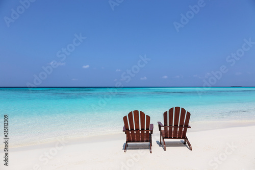 Two adirondack chairs on sunny, tranquil beach overlooking blue ocean, Maldives, Indian Ocean - 315112309