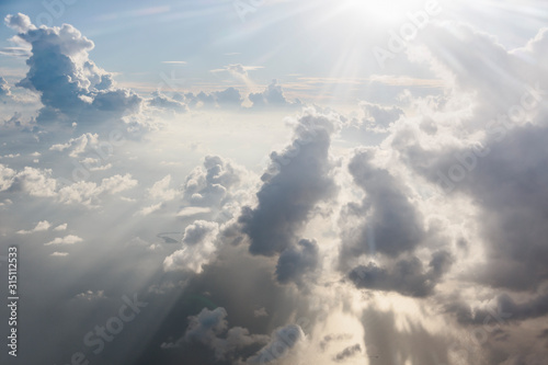 Aerial view sunbeams and fluffy white clouds in ethereal sky - 315112533