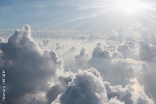 Aerial view sunbeams over fluffy clouds in sky - 315112539