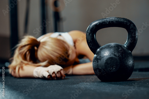 Obraz na plátně Young exhausted girl lying on a floor of fitness center after training