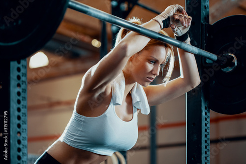 Fotografia Tired fit girl taking break after weight lifting in professional gym