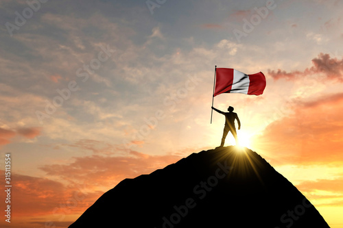 Peru flag being waved at the top of a mountain summit Wallpaper Mural