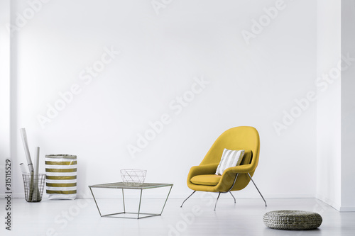 Real photo of a minimalistic living room interior with a yellow armchair. Empty, white wall. Place your poster - 315115529