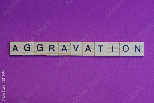 Photo word aggravation from small gray wooden letters lies on a lilac background