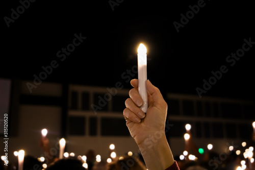 One single hand arm holding up a LED candle amongst a crowd of lights at a candl Fototapeta
