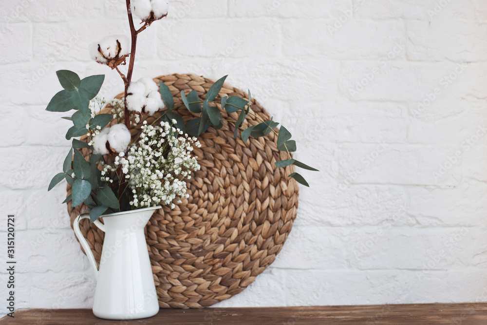 Fototapeta vase with flowers and a photo frame at home on a wooden table.