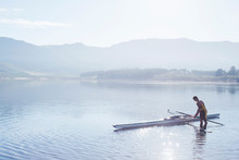 Man Placing Rowing Scull In Lake