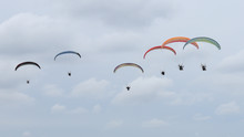 A Group Of Colorful Powered Paragliders Flying In The Blue Sky With Clouds In The Background