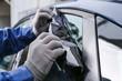 Male worker tinting car window, closeup
