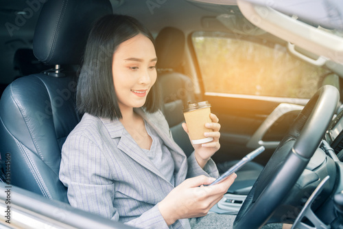 Fototapety, obrazy: Asian woman talk by mobile calling texting and looking on a cellular phone while drinking coffee sitting in her car, driving under the influence, the driver is safely talking by smartphone car concept