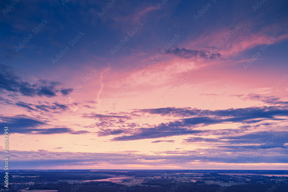 Fototapeta Aerial view of countryside in evening at sunset light. Beautiful nature landscape with cloudy sky
