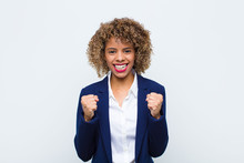 Young Woman African American Shouting Aggressively With Annoyed, Frustrated, Angry Look And Tight Fists, Feeling Furious Against Flat Wall