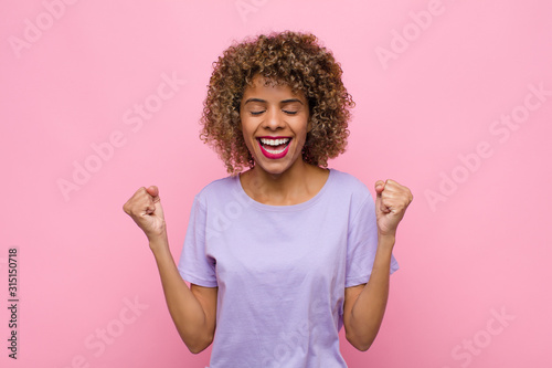 young african american woman looking extremely happy and surprised, celebrating Wallpaper Mural