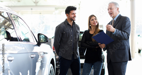 Photographie Car dealer exaplining a car's features to a couple by reading a document