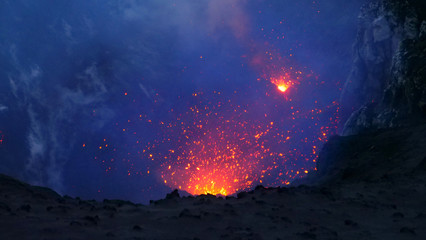CLOSE UP: Active volcano in the Pacific spewing out the glowing orange lava.