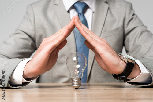 Photo cropped view of businessman showing protection gesture above light bulb isolated