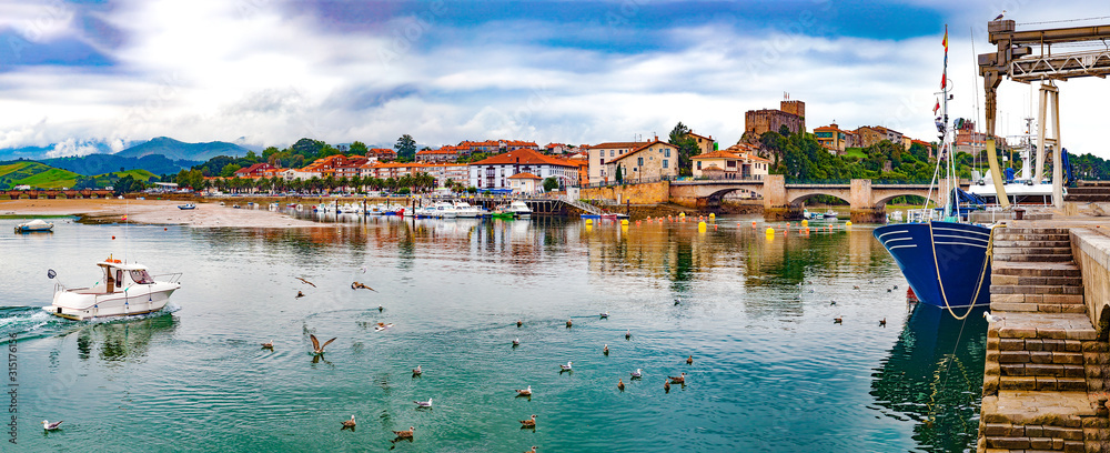 Fototapeta San Vicente de la barquera village in Cantabria,Spain.Scenic medieval village ,mountain and sea panoramic landscape in northern Spain.Green meadows and boats in the port