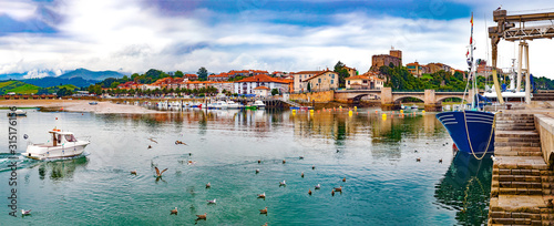 San Vicente de la barquera village in Cantabria,Spain.Scenic medieval village ,mountain and sea panoramic landscape in northern Spain.Green meadows and boats in the port