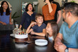 Happy family with birthday cakes on table enjoying at home