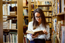 Female Student In Library Reading A Book, Looking For Materials To Make Research