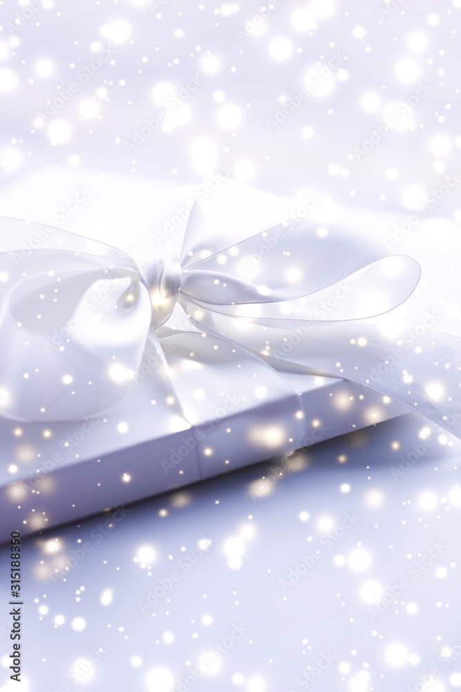 Winter holiday gift and glowing snow background, Christmas presents surprise