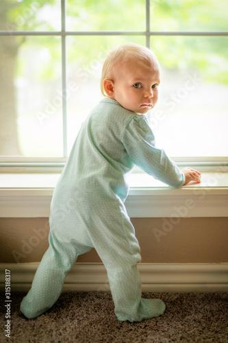Vászonkép Beautiful baby girl wearing footie pajamas