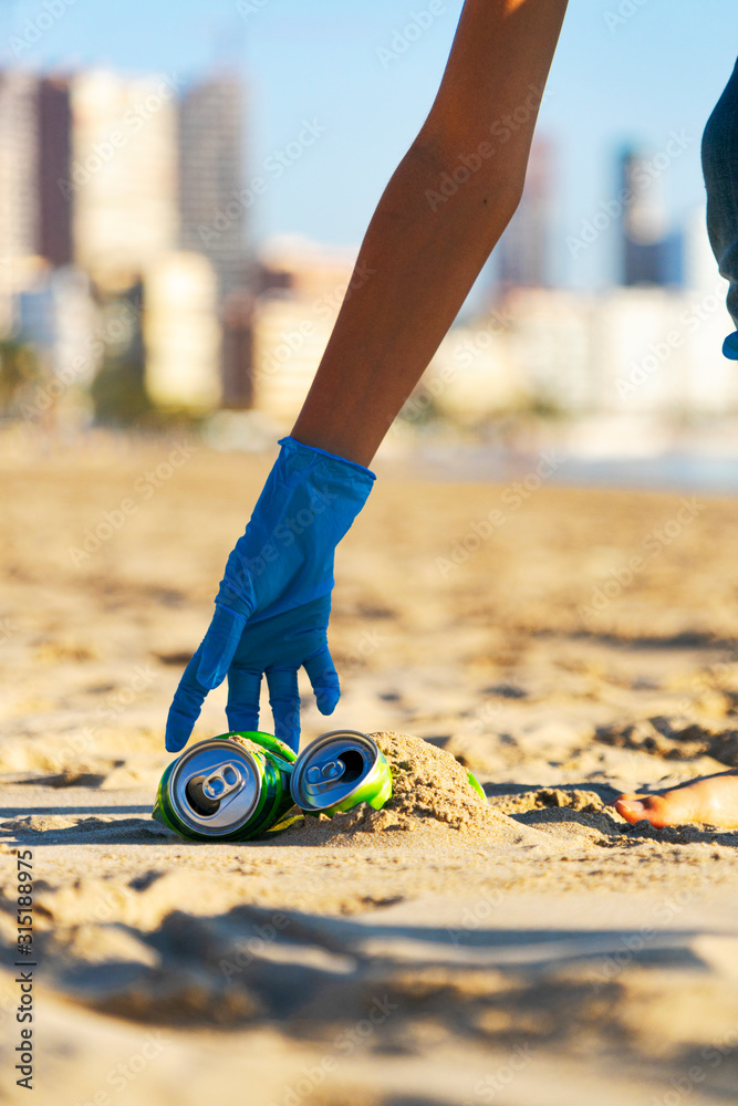 Fototapeta Clean beach from trash. Woman hand picking up empty soft drinks cans trash from the beach