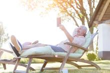 Senior Man Using Digital Tablet Relaxing On Lounge Chair In Backyard