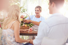 Florist Discussing Flowers With Couple In Flower Shop