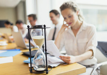 Hourglass In Front Of Businesswoman Reviewing Paperwork In Conference Room