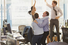 Exuberant Business People Celebrating And Jumping In Office