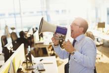 Exuberant Businessman Shouting Into Megaphone In Office