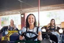 Portrait Smiling Young Woman Riding Bumper Cars At Amusement Park