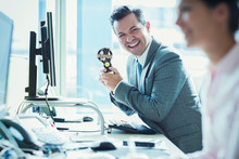 Portrait Enthusiastic Businessman Holding Winner Trophy At Desk In Office