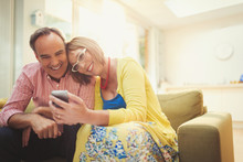 Smiling Mature Couple Texting With Cell Phone In Living Room