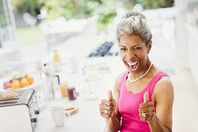 Portrait Enthusiastic Confident Mature Women Gesturing Thumbs-up In Kitchen