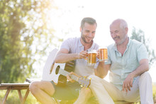 Father And Adult Son Toasting Beer Mugs And Playing Guitar Outdoors