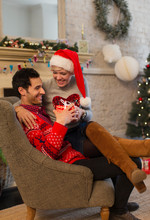Affectionate Couple Opening Christmas Gifts In Living Room