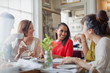 Smiling women friends dining drinking coffee at restaurant table