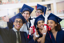 Happy College Students In Cap Gown Holding Diplomas Posing For Selfie