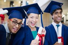 Portrait Enthusiastic College Graduates In Cap Gown Holding Diplomas