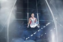 Focused Male Gymnast Performing On Gymnastics Rings In Arena