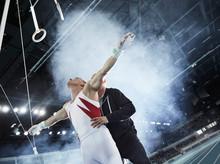 Coach Lifting Male Gymnast Bel...