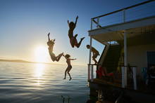 Young Adult Friends Jumping Off Summer Houseboat Into Sunset Ocean