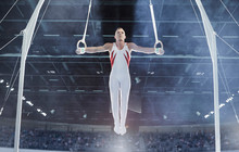 Male Gymnast Balancing Arms Outstretched On Gymnastics Rings In Arena