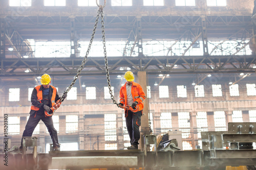 Photo Steel workers with crane hooks in factory