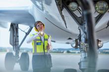 Ground Crew Worker Under Airplane With Flashlight On Airport Tarmac
